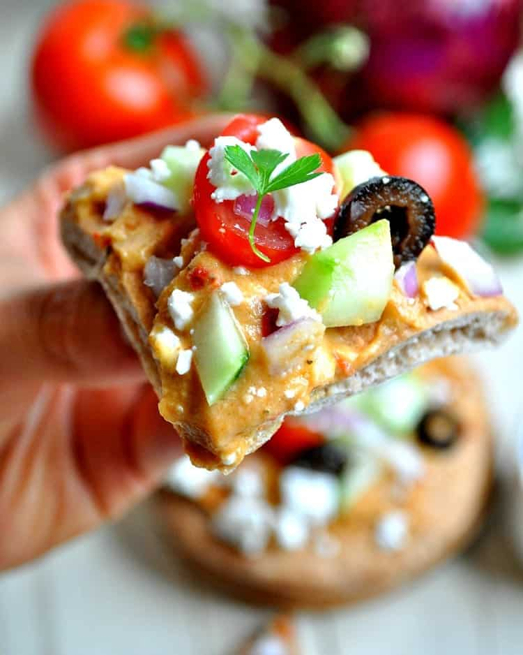 A close up of Greek pita bread bite topped with olives, feta and tomato