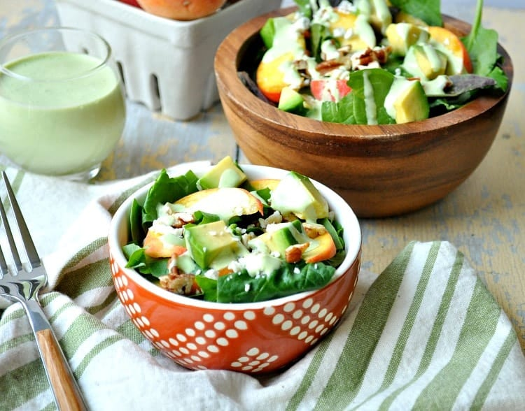 Peach Salad in two bowls with some green dressing in a glass