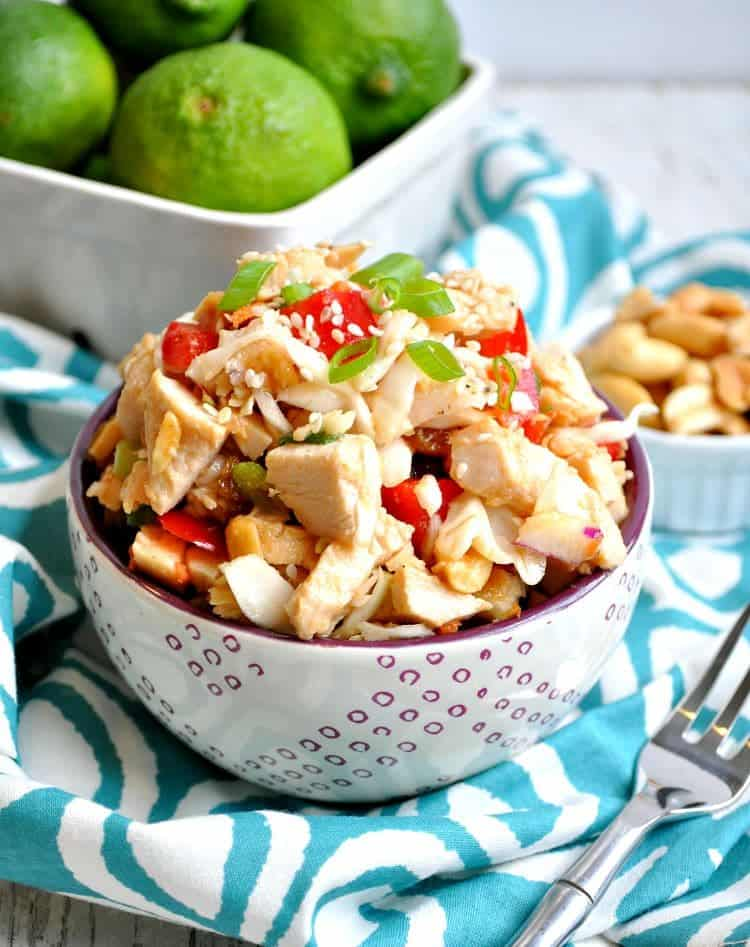 Thai Peanut Chicken Salad in a white bowl with a fork at the side
