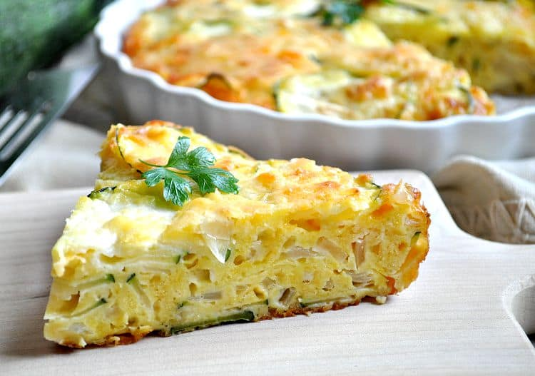 A slice of zucchini pie topped with parsley