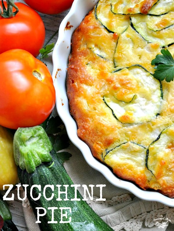 A corner of a zucchini pie with summer vegetables at the side