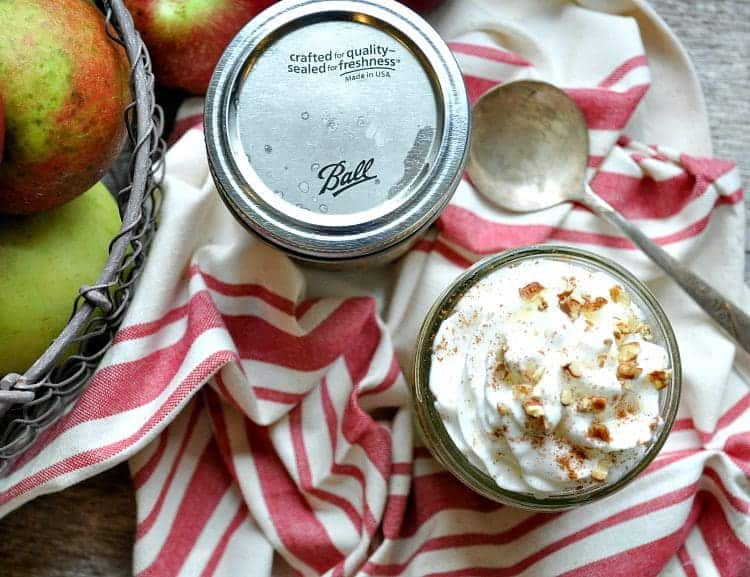 An overhead shot of mason jars filled with apple breakfast parfait and whipped cream