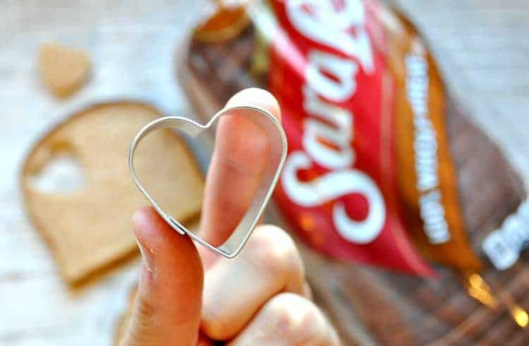 A hand holding a heart shaped cookie cutter