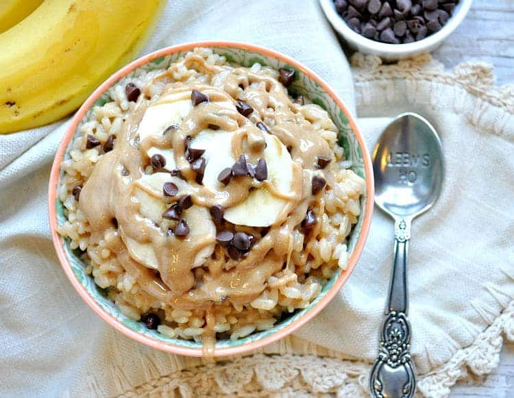 An overhead shot of a Healthy Chunky Monkey Dessert Rice Bowl with a spoon at the side