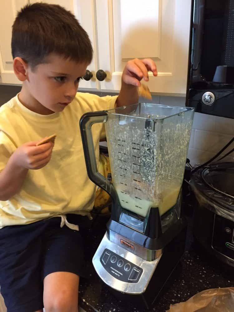 A boy making blender muffins in the kitchen