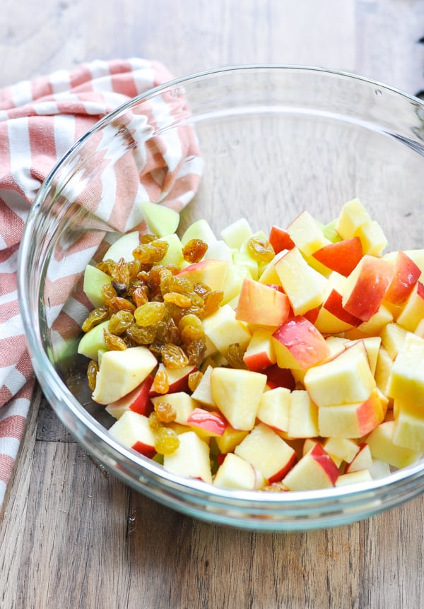Glass bowl full of chopped apples and golden raisins