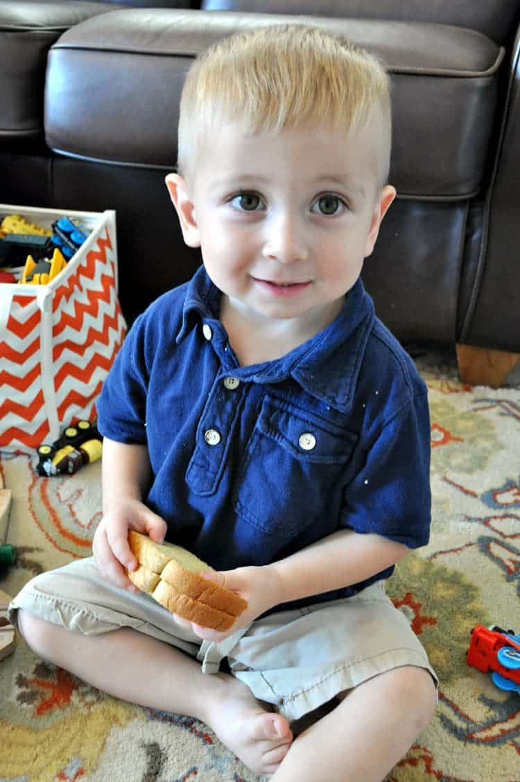 A small boy eating a Peanut Butter and Jelly sandwich