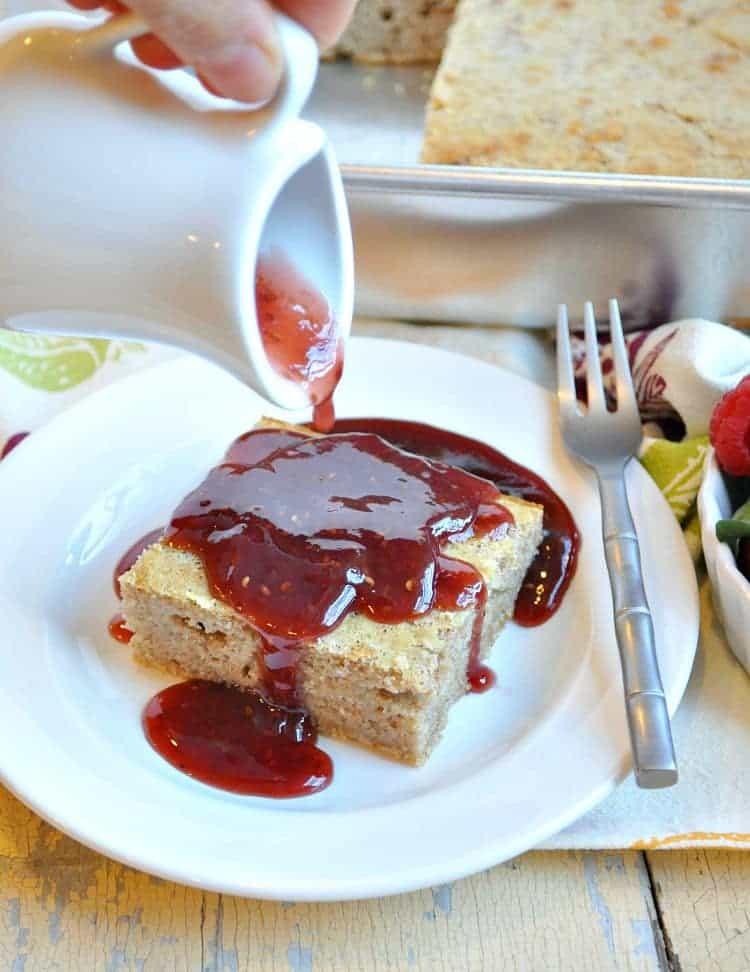 A slice of baked pancakes on a plate with jelly sauce getting poured over