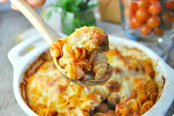 Close up of wooden spoon with meatball and pasta casserole on it for serving