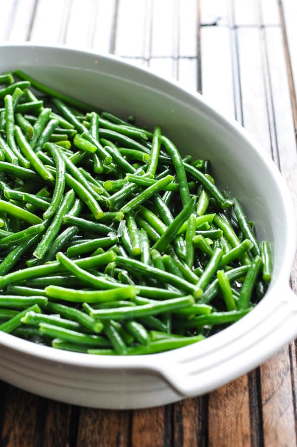 Fresh green beans in white baking dish