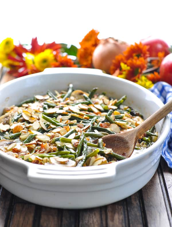 Front view of fresh green bean casserole with bacon and a wooden serving spoon