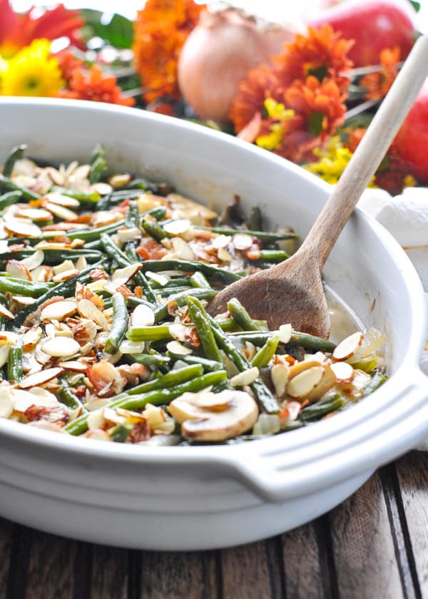 White baking dish with green bean casserole with bacon