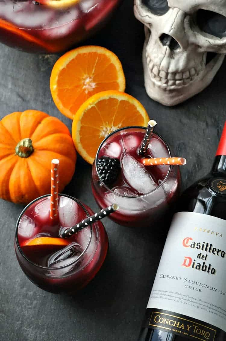 Overhead image of glasses of sangria surrounded by Halloween decorations
