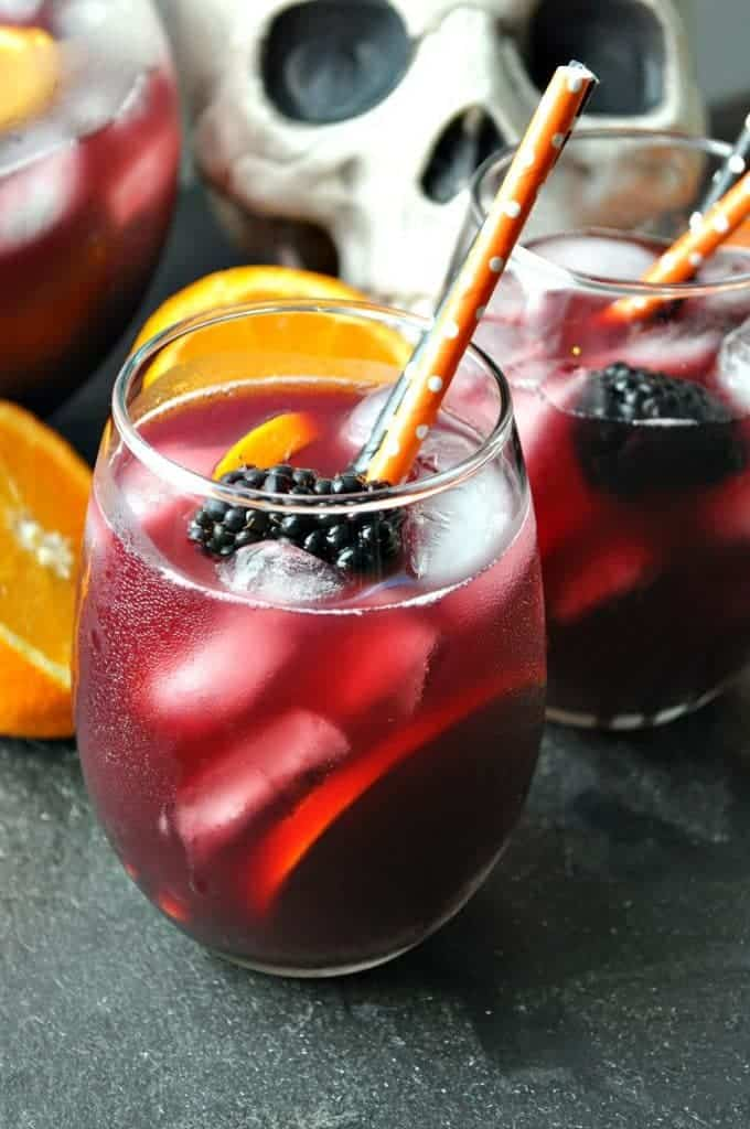 Glass of red wine sangria with orange and black fruit for Halloween party