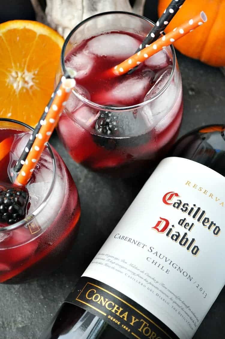 Overhead image of two glasses of sangria with oranges and bottle of red wine