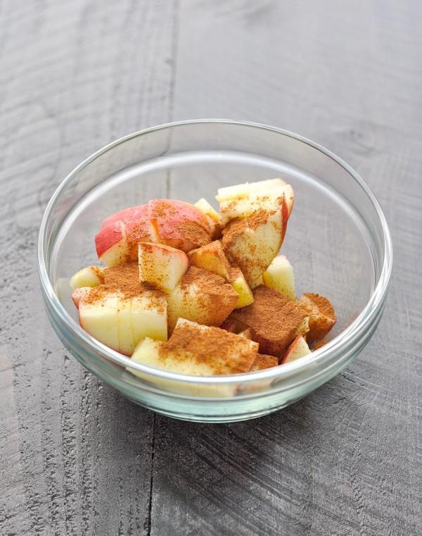 Diced apple with cinnamon in glass bowl