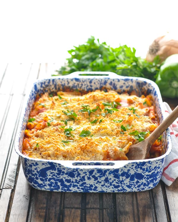 Front view of Chicken Parmesan Casserole in a baking dish with a wooden spoon