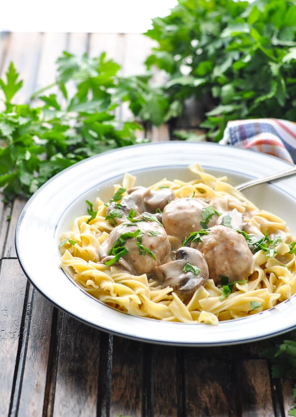 Front view of slow cooker meatball stroganoff and egg noodles in bowl with fork