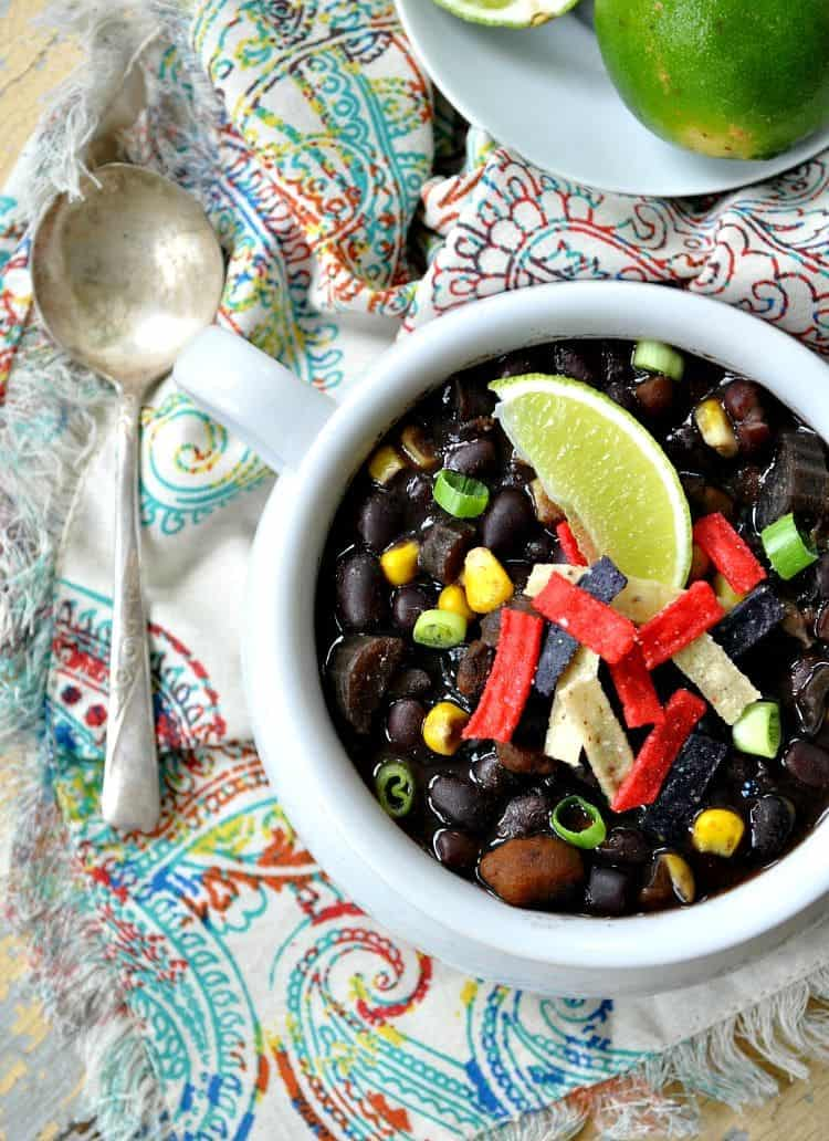 An overhead shot of slow cooker black bean soup in a bowl topped with lime wedges
