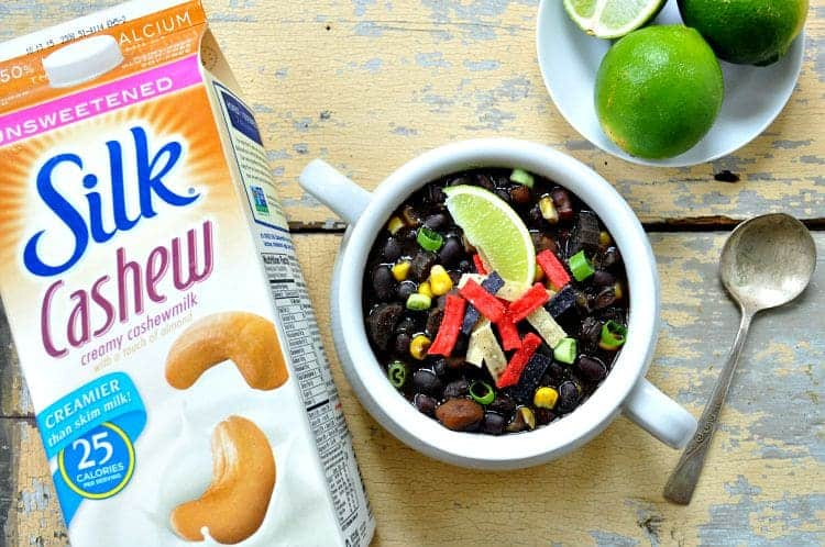 An overhead shot of silk cashew milk in a carton and a bowl of slow cooker black bean soup