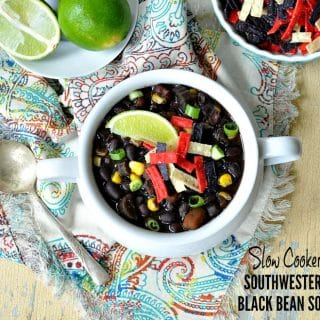 A bowl of slow cooker black bean soup sitting on a wooden surface