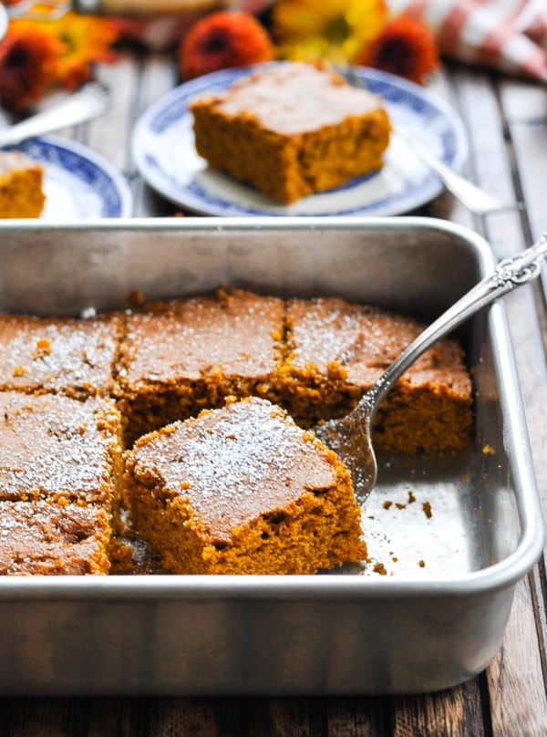 Pan of pumpkin gingerbread cake dusted with powdered sugar and slice on a serving fork