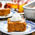 Pumpkin Gingerbread Cake on a plate and topped with whipped cream