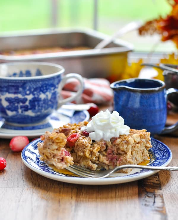 Cranberry baked oatmeal topped with whipped cream with a fork on a plate