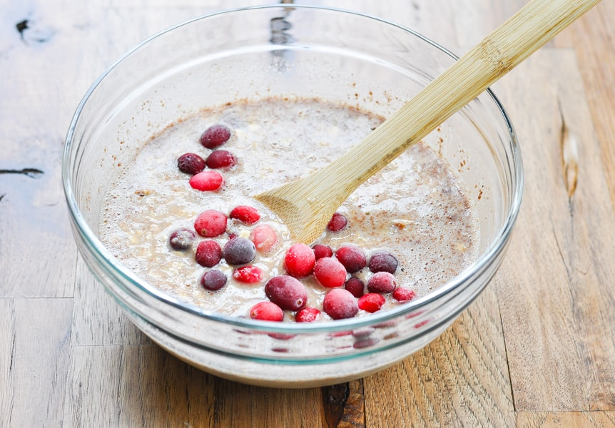 Combined ingredients with frozen cranberries for baked oatmeal in a glass bowl