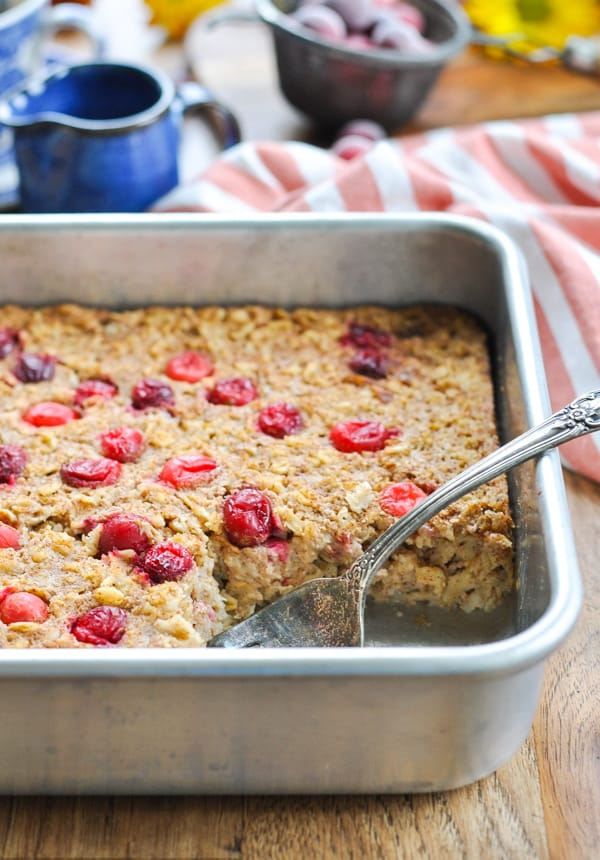 Cranberry baked oatmeal in a baking dish with a serving spoon