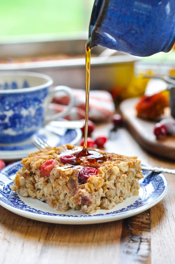 Pouring maple syrup over a slice of cranberry baked oatmeal
