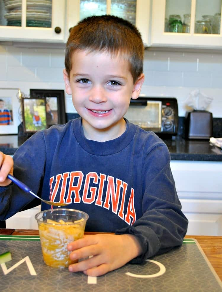 A boy eating mac and cheese cups with a spoon