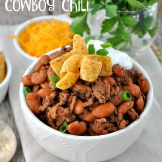 A cowboy chili in a white bowl topped with green onions and sour cream