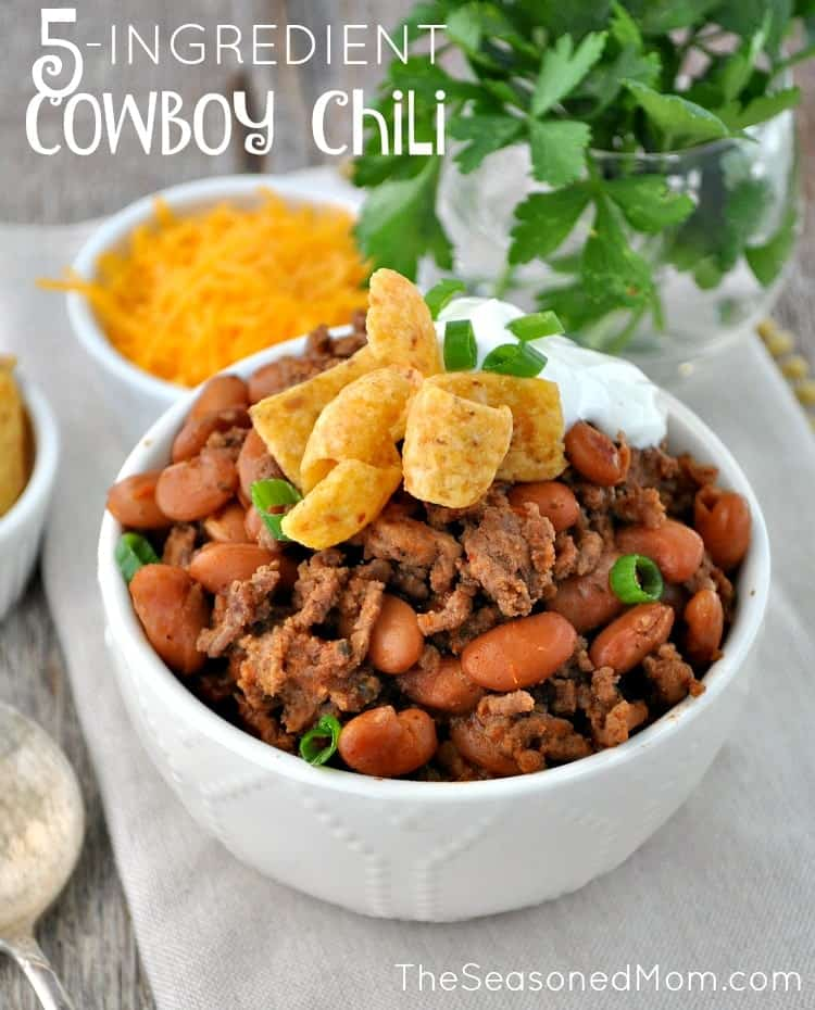 Cowboy Chili in a white bowl topped with chips and sour cream