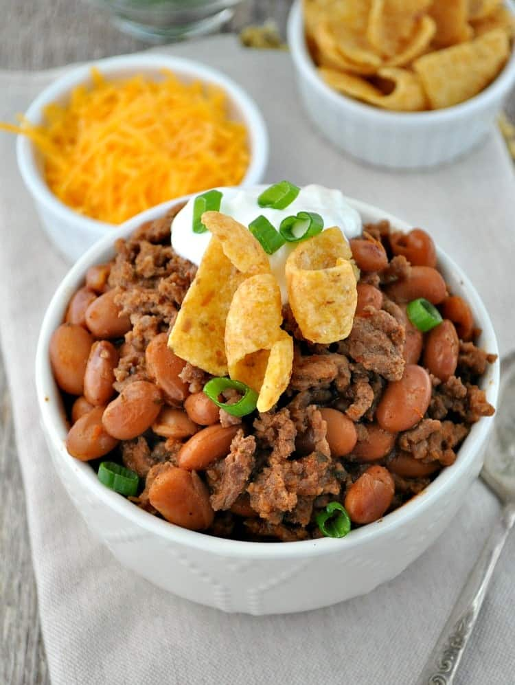 Cowboy Chili in a white bowl topped with sour cream and scallions