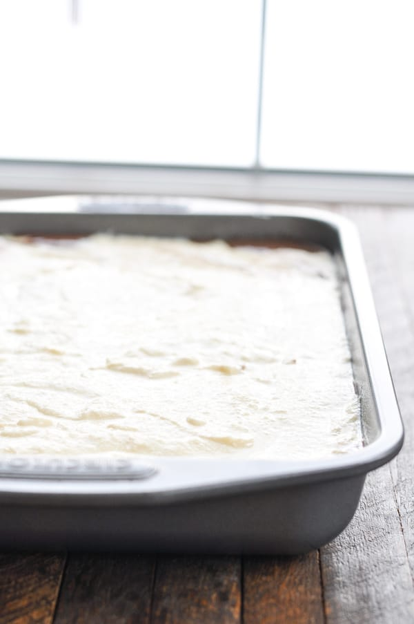 Ricotta layer poured over chocolate cake batter in baking dish before oven