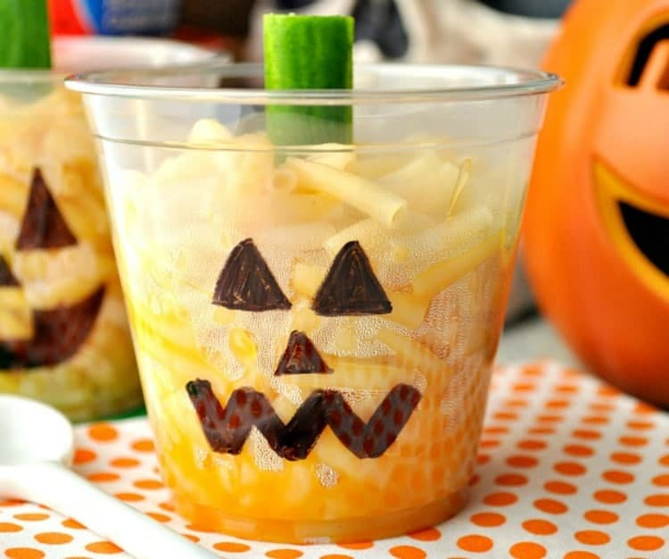 A close up of Jack-O-Lantern Mac & Cheese Cups topped with cucumbers