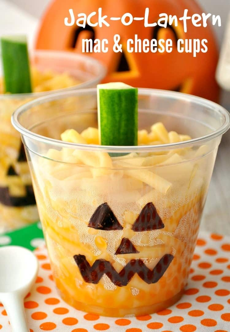 A close up of a mac and cheese cup in a halloween pumpkin cup