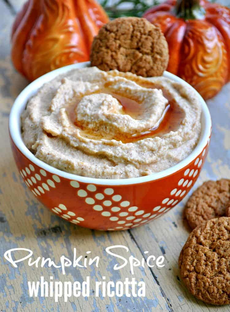 A close up of pumpkin spice whipped ricotta in a bowl with ginger cookies at the side