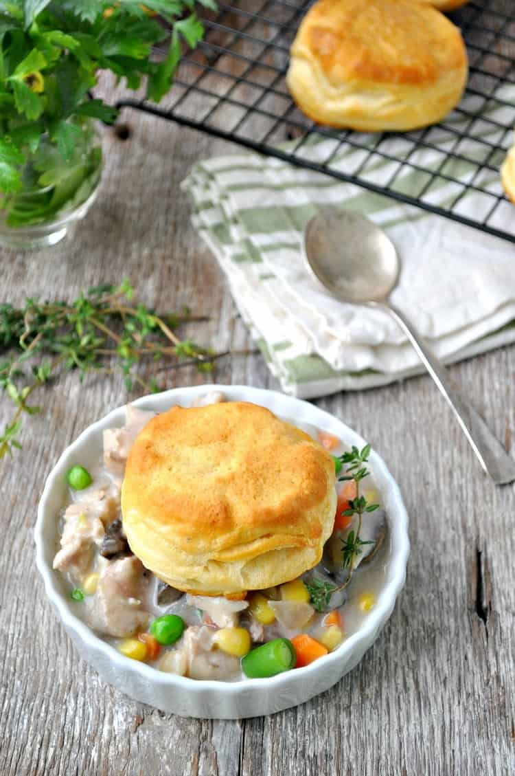 Chicken and biscuits in a white dish with herbs behind it