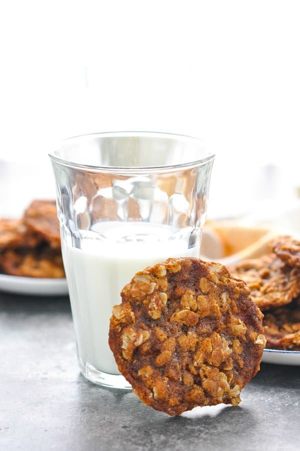 Easy oatmeal cookie propped against a glass of milk
