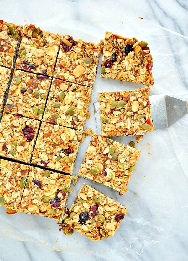 Sliced fall harvest healthy granola bars on a cutting board with spatula