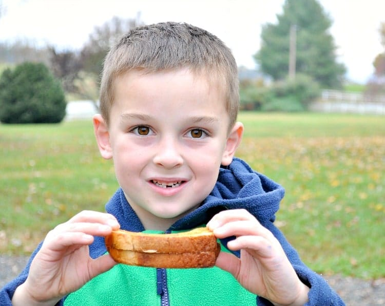 A boy holding a peanut butter and jelly sandwich