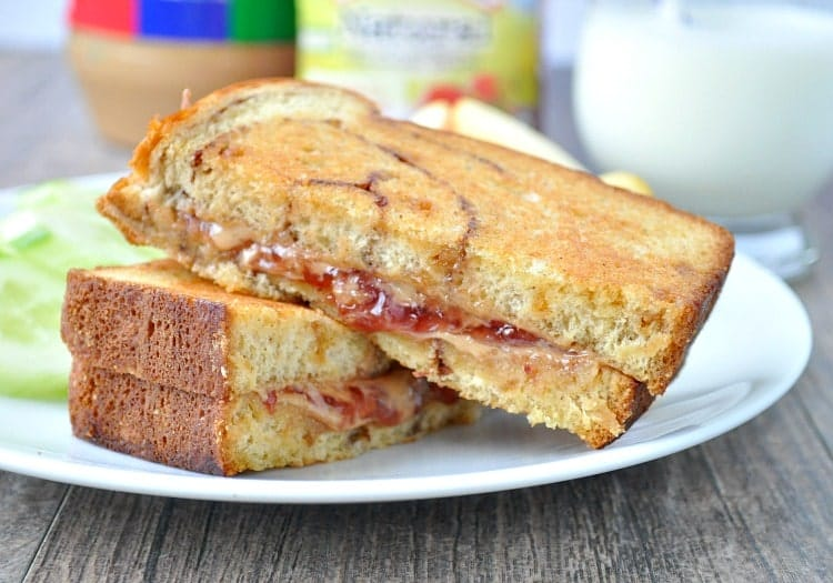 A close up of a cut peanut butter and jelly sandwich