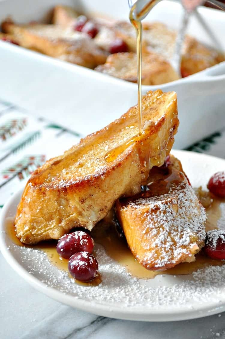 Overnight French Toast Casserole on a white plate topped with syrup