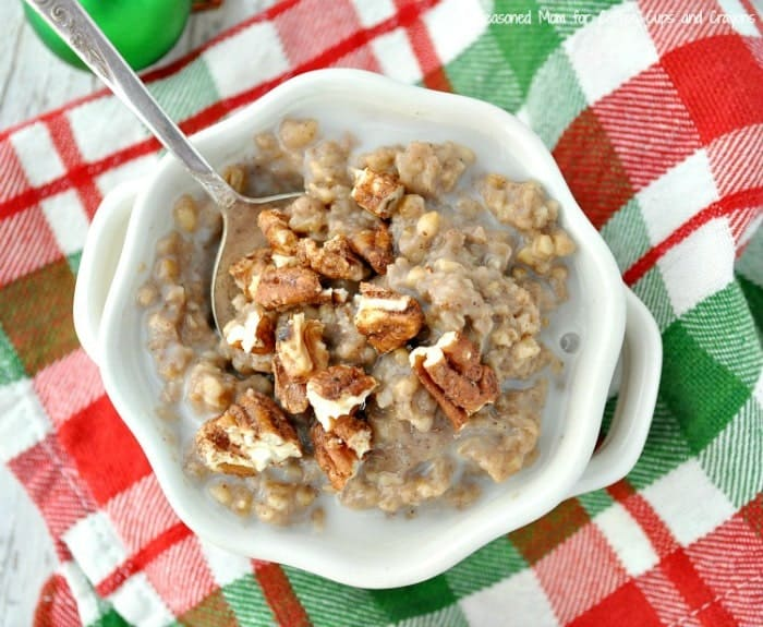 An overhead shot of gingerbread Slow Cooker Oatmeal in a white bowl topped with pecans