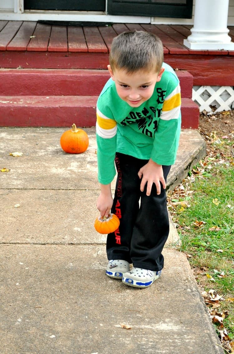 Child holding mini pumpkin for Turkey Bowling game
