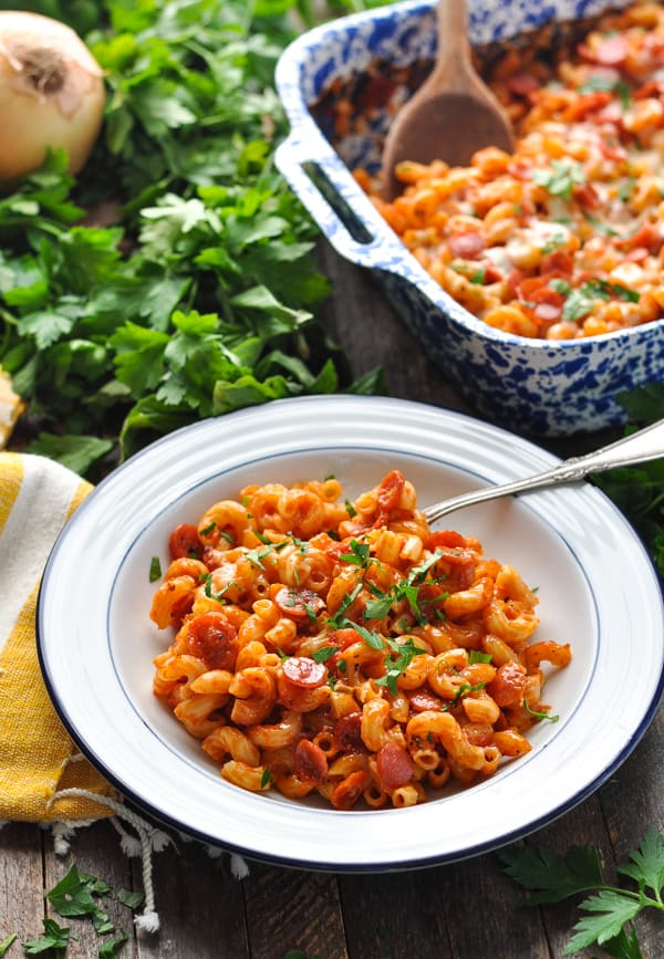 Bowl of pizza casserole with pasta and fresh herbs