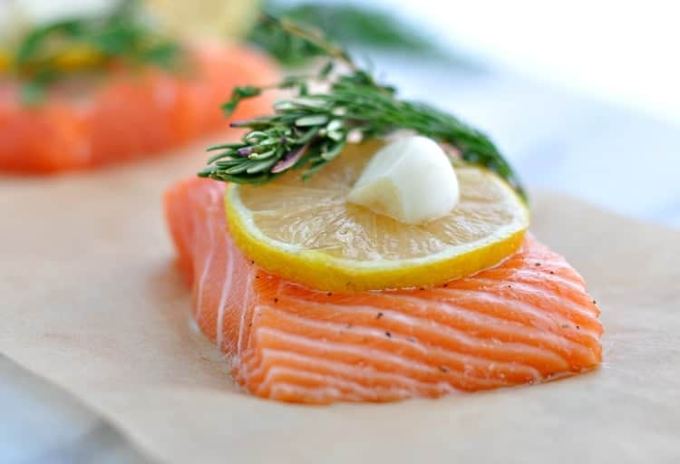 A fillet of salmon topped with lemon and herbs