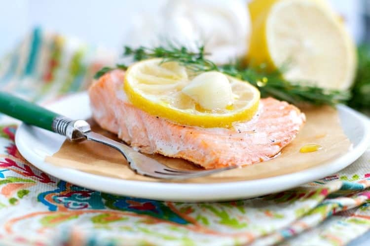 A fillet of baked salmon on a plate with lemon